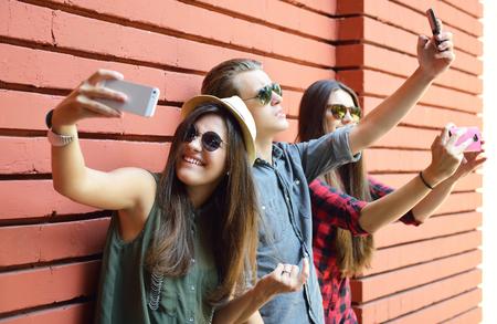 Los jóvenes se divierten al aire libre y hacer selfie con el teléfono inteligente contra la pared de ladrillo rojo. Forma de vida urbana, la felicidad, la alegría, amigos, auto foto concepto de red social. Imagen de tonos y ruido añadido. Foto de archivo