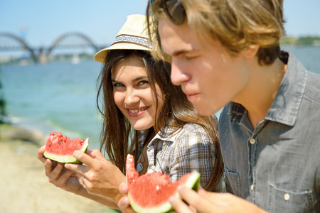 frienship: Happy young couple eating watermelon on the beach. Youth lifestyle. Happiness, joy, frienship, holiday, beach, summer concept. Group of young people having fun outdoor. Stock Photo