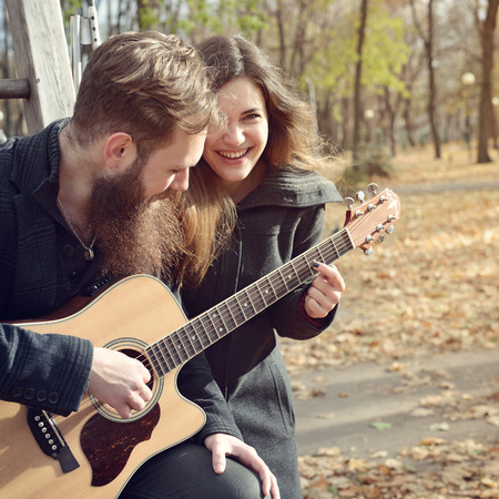 bigote: Pareja joven tocando la guitarra juntos en el otoño de parque al aire libre, imagen de tonos y ruido añadido. Hombre inconformista con la barba y el bigote con su bella novia sonriente feliz divertirse al aire libre.