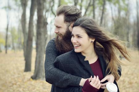 Fashion portrait d'un jeune couple de boire du café dans le parc de l'automne en plein air, Image teintée et le bruit ajouté. Hipster homme avec barbe et la moustache embrassant sa petite amie belle sourire heureux en dehors.