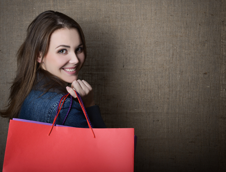 color model: Young happy smiling woman holding red and purple shopping bags over canvas, image toned.
