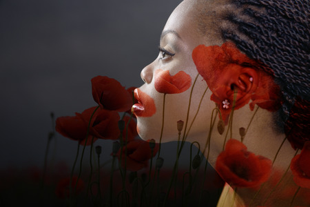 woman profile: Double exposure portrait of beautiful woman. Beauty portrait of young african woman in profile with summer poppy flowers over dark gray background