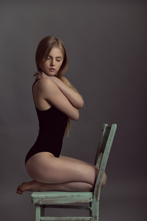 sudio: Portrait of young blond woman posing in sudio with retro obsolete chair over gray background.