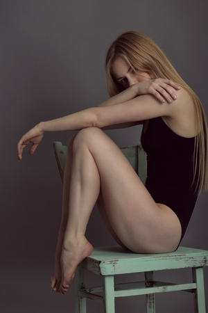 sexy teen: Portrait of young blond woman posing in sudio with retro obsolete chair over gray background.
