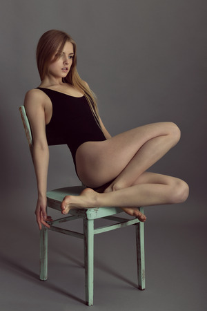 Portrait of young blond woman posing in sudio with retro obsolete chair over gray background.
