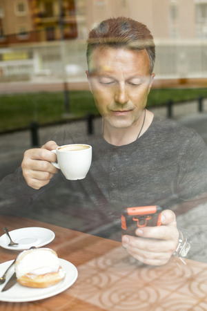 Attractive mid adult man drinking morning coffee in cafe and using smart phone. Stock Photo