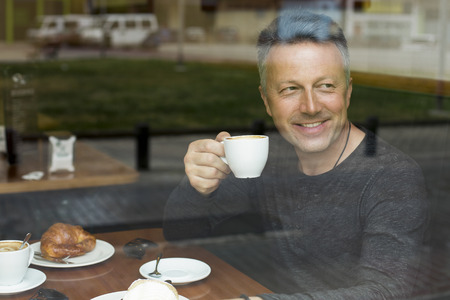 mid morning: Attractive smiling mid adult man drinking morning coffee in cafe, image toned.