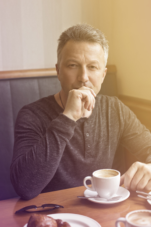 Attractive mid adult man drinking morning coffee in cafe, image toned. Stock Photo