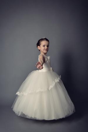 Little Princess posing in evening dress. Little girl dancing ballet in studio over gray background. Stock Photo