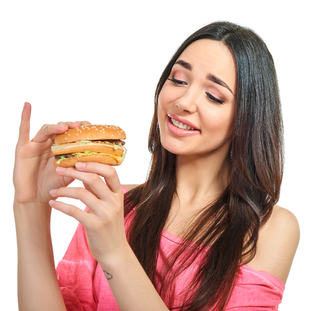 Young happy attractive woman with fast food. Unhealthy eating. Stock Photo