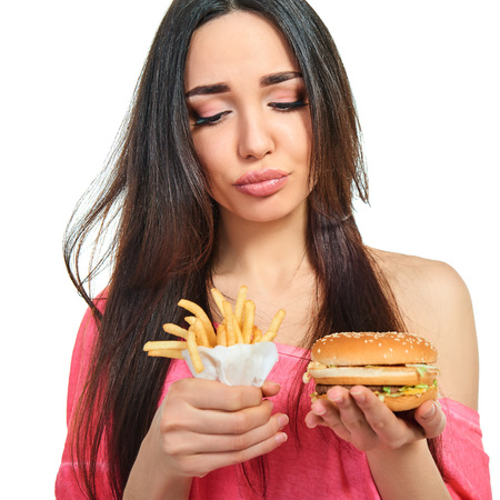 Young woman with fast food. Girl eating hamburger and fries over white background. Unhealthy eating. Stock Photo