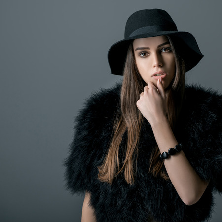 Young beautiful sexy woman in black with hat over gray background. Fashion female portrait.