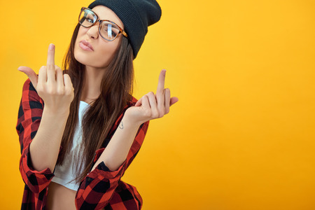 audacious: Fashion beauty girl wearing sunglasses, plaid shirt, black beanie hat. Young woman showing middle finger over yellow background. Stock Photo