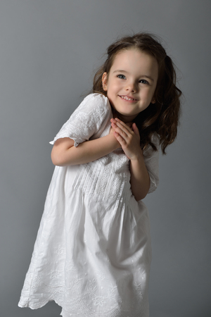 petite fille avec robe: Sweet little happy girl in white dress, studio portrait over gray background