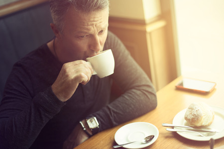 Attractive mid adult man drinking morning coffee in cafe, image toned Stock Photo