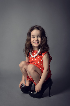 girl shoes: Little fashionista. Little beautiful fashion girl posing in mothers high heels shoes and happy smiling.