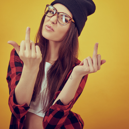 Fashion beauty girl wearing sunglasses, plaid shirt, black beanie hat. Young woman showing middle finger over yellow background. Image toned.