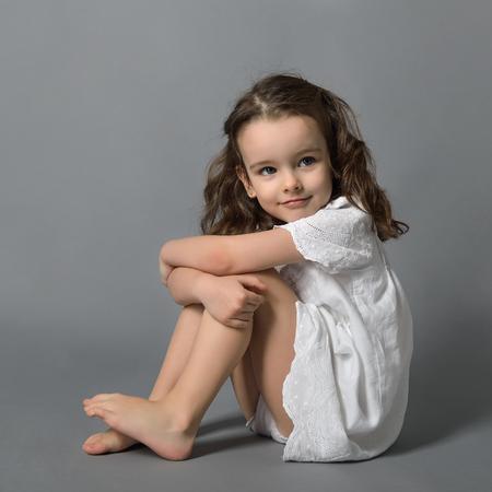 Zoet klein gelukkig meisje in witte jurk, studio portret over grijze achtergrond