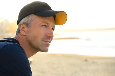 manful: Handsome man. Outdoor male portrait. Middle-aged man resting at the beach, summer outdoor portrait, image toned. Saint Jean de Luz, France.