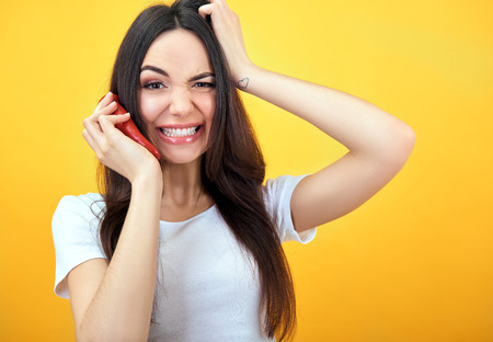 Hipster girl holding red hot chilli pepper near her face like smartphones and screaming over yellow background.