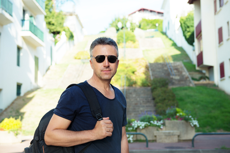 manful: Male outdoor street portrait. Mid adult man walking at summer city Saint Jean de Luz streets, France.