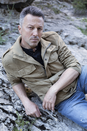 manful: Outdoor male portrait. Handsome middle-aged man sitting on rocks, image toned and noise added.