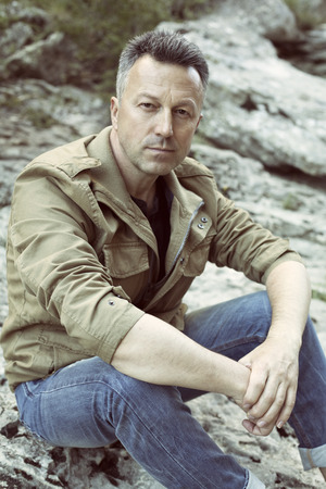 manful: Outdoor male portrait. Handsome middle-aged man sitting on rocks and looking at camera, image toned and noise added. Stock Photo