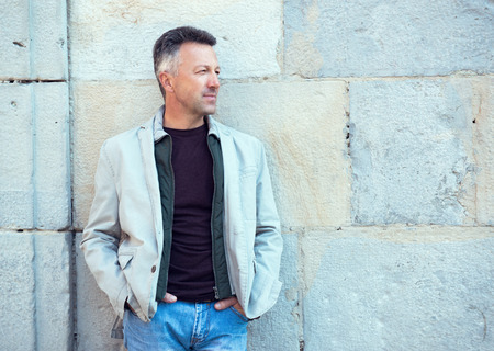 manful: Handsome middle-aged man posing over old ancient street wall, Pamplona, Spain. Outdoor male portrait, image toned. Street photo. Stock Photo
