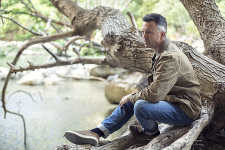 manful: Outdoor male portrait. Man sitting on trees branch near mountain river, image toned and noise added. Stock Photo