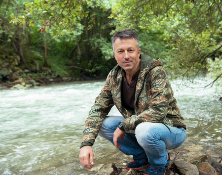 manful: Outdoor autumn male portrait. Man sitting on rocks near mountain river, image toned and noise added.