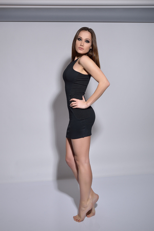 Beatiful model posing at studio over gray background