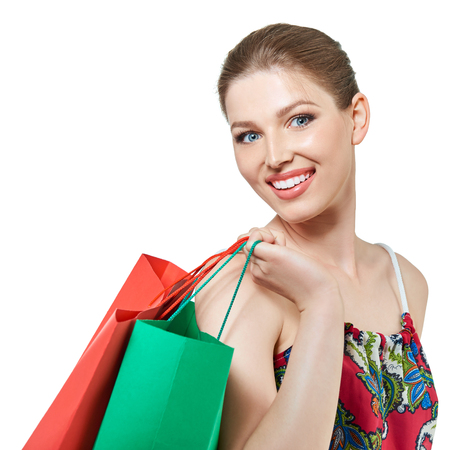 Shopping woman holding shopping bags looking at camera. Beautiful young female shopper smiling happy, isolated on white.