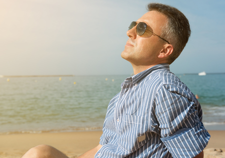 Man is sunbathing on sea coast, summer nature outdoor. Portrait of handsome middle-aged man rests on the beach, image toned.