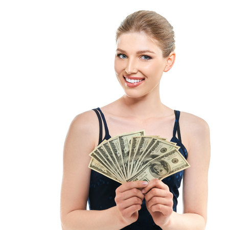 Young happy woman holding cash money dollars happy smiling and looking at copyspace in top left corner of picture, isolated on white background. Stock Photo