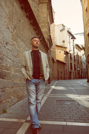 manful: Handsome middle-aged man posing over old ancient street, Pamplona, Spain. Outdoor male portrait, image toned.