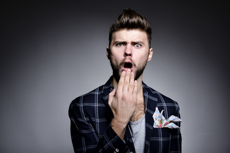 Portrait of young man wriggles in studio over gray background. Hypster gay covers open mouth with his hand. grimanced, fright, fear, surpriced, grotesque. Stock Photo - 78431034