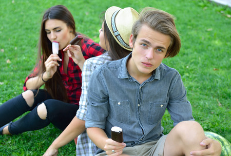Young man and women eating chocolate ice-cream outdoor in summer park. Friends have fun outdoor. Leaisure, youth, summertime. photo