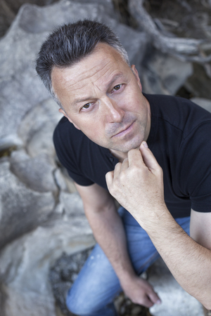 manful: Outdoor male portrait. Handsome middle-aged man sitting on rocks and looking at camera. Stock Photo