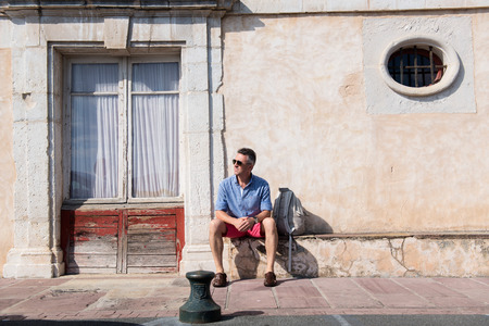 manful: Handsome man. Outdoor male portrait. Middle-aged man sitting near ancient european house against obsolete wall, summer outdoor portrait, image toned.