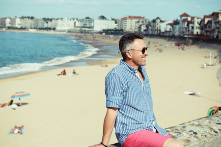 manful: Handsome man. Outdoor male portrait. Middle-aged man resting at seafront, summer outdoor portrait, image toned.