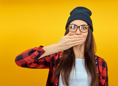 Excited surprised young woman covers hands open mouth over yellow background. Emotional female portrait. Hipster girl. Stock Photo