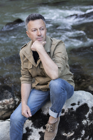 manful: Outdoor male portrait. Handsome middle-aged man sitting on rocks near mountain river, image toned and noise added.