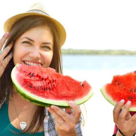 Happy young couple eating watermelon on the beach. Youth lifestyle. Happiness, joy, frienship, holiday, beach, summer concept. Group of young people having fun outdoor. Enjoy life, youth and summer. photo