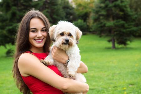 Girl with puppy. Portrait of attractive happy smiling young woman holding cute little dog, summer park outdoor. Stock Photo