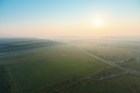 Amazing view from the height of the balloon. Summer beautiful fields lanscape from the birds eye, sunrise. Ballooning.