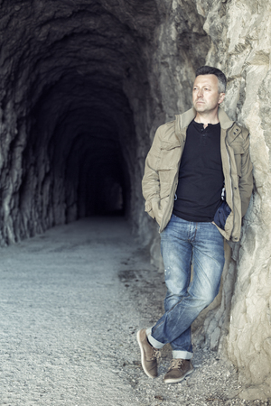 manful: Outdoor male portrait. Man standing near tunnel, image toned. Stock Photo