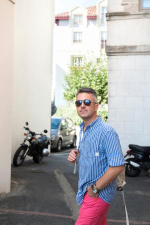 manful: Male outdoor street portrait. Mid adult man walking city Saint Jean de Luz streets, France.