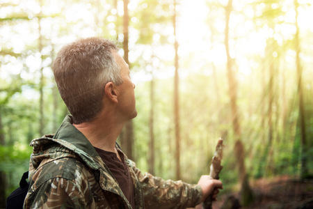 manful: Man in forest looking at sunlight. Insight, soft focus, image toned and noise added.