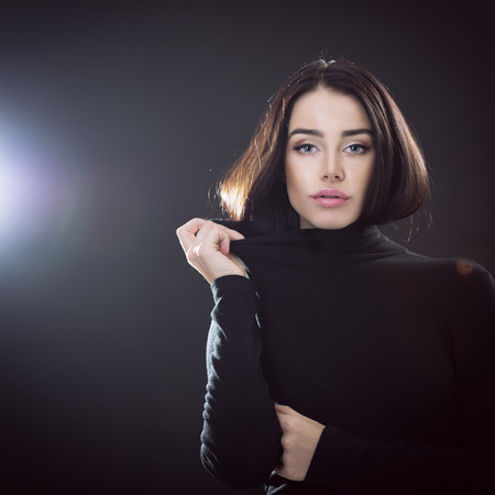 goodly: Beautiful girl posing over black background. Young pretty woman in studio. Stock Photo