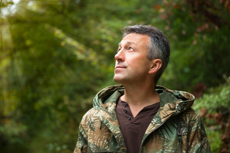 inscrutable: Handsome man in forest looking at sunlight. Insight, soft focus, image toned and noise added. Sun after the rain.